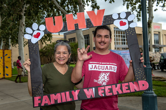 UHV family posing at Family Day with a photo frame
