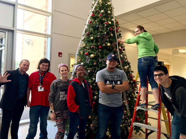 Michael Wilkinson, director of UHV Student Life & Services, helps decorate the UHV Giving Tree on Monday with freshman seminar students.