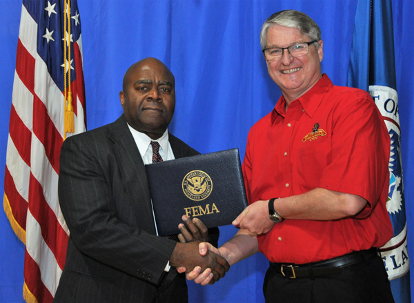 Stuart Sherman, UHV emergency management assistant fire marshal, graduates from FEMA'S Emergency Management Institute on March 29 and is congratulated by Tony Russell, superintendent of the FEMA Institute in Emmitsburg, Md.