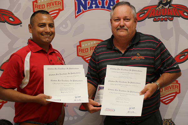 George Rodriguez and Paul Ebner show some of the nine awards received at the College Sports Information Directors of America Summer Convention for marketing pieces