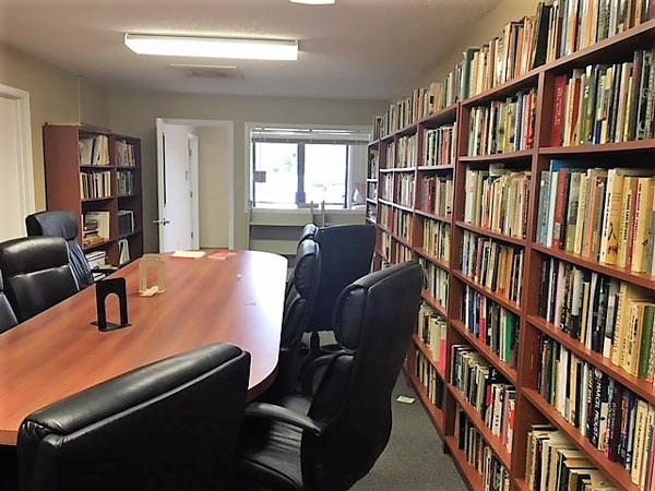 photo of an empty UHV conference room with a full bookshelf on the right