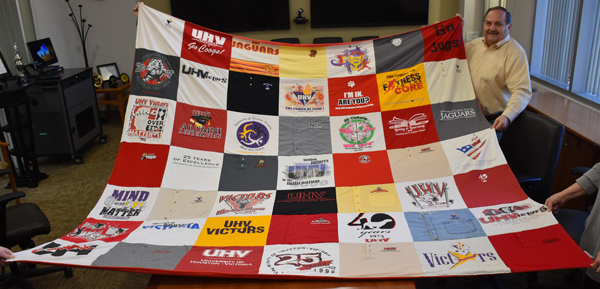 UHV retiree Joe Ferguson displays a quilt Thursday that he had made from 49 shirts he accumulated during his 42 years working at UHV