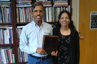 Mel Damodaran, left, a professor of math and computer science at the University of Houston-Victoria, and his wife, Padmini, hold a plaque he received from the School of Arts & Sciences for his nearly 20 years of service at the university.
