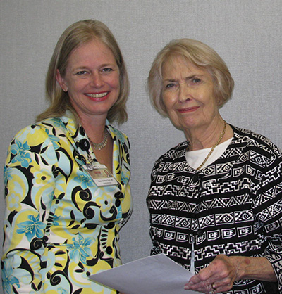 Julia Martin, right, holds a signed agreement with Kathryn Tart to establish the Dr. Thomas L. Martin Scholarship for graduate nursing students.
